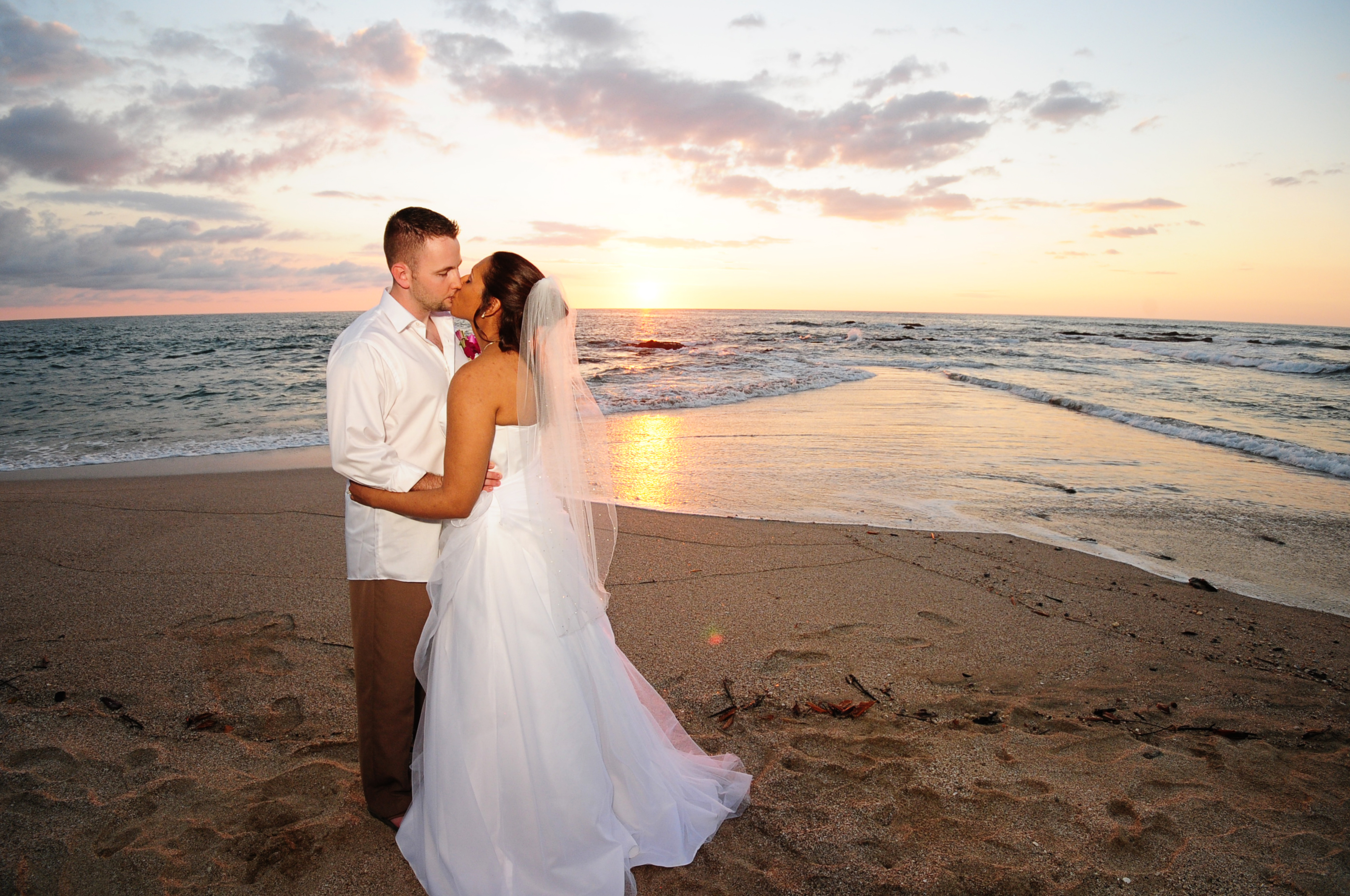 Beach Wedding Couple Kissing After Ceremony